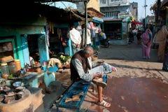 Vieil homme asiatique lisant un journal de matin Images stock