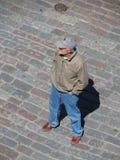 Vieil homme attendant sur une place Photo stock