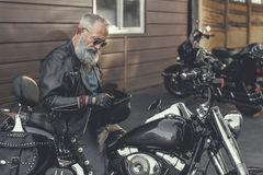 Vieil homme attentif gardant le claquement de vélo Photographie stock libre de droits