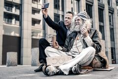 Vieil homme aux cheveux gris enthousiaste étant extrêmement heureux avec l'argent image stock