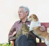 Vieil homme avec des animaux familiers Image libre de droits