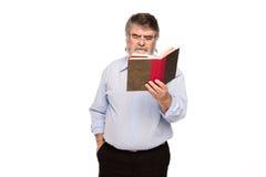 Vieil homme avec des verres lisant un livre Photographie stock libre de droits