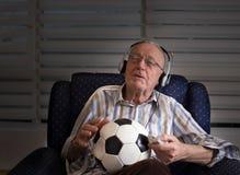 Vieil homme avec du ballon de football regardant la TV Photographie stock