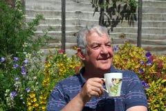 Vieil homme avec du café d'ofd de cuvette. Images stock