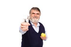 Vieil homme avec l'eau et la pomme Photographie stock libre de droits