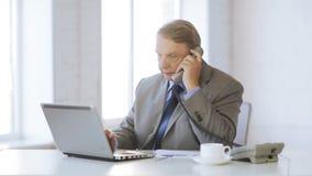 Vieil homme avec l'ordinateur portable prenant un appel téléphonique banque de vidéos