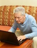 Vieil homme avec l'ordinateur portatif Images stock