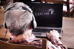 Vieil homme avec l'ordinateur portatif Photographie stock