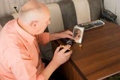 Vieil homme avec la lotion après-rasage regardant le miroir Image stock