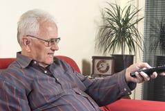 Vieil homme avec la télévision à télécommande Photos stock