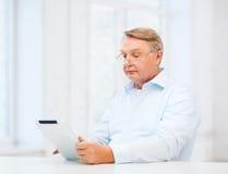 Vieil homme avec la tablette à la maison Photographie stock libre de droits