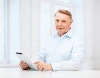 Vieil homme avec la tablette à la maison Photos libres de droits