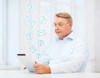 Vieil homme avec la tablette à la maison Images libres de droits