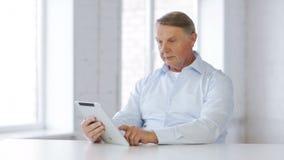 Vieil homme avec la tablette à la maison banque de vidéos