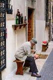 Vieil homme avec le chapeau et la canne se reposant devant une boutique de vin Image stock
