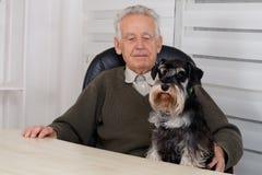 Vieil homme avec le chien noir de Schnauzer miniature Photo libre de droits