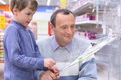 Vieil homme avec le garçon avec le gril pour la torréfaction Photo stock