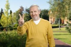 Vieil homme avec le geste de victoire Photo stock