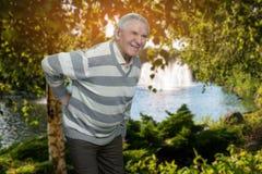 Vieil homme avec le mal de dos extérieur Photographie stock