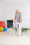 Vieil homme avec le marcheur en physiothérapie Photos stock