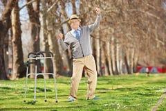 Vieil homme avec le marcheur faisant des gestes le bonheur dehors Photo libre de droits