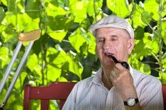 Vieil homme avec le tuyau de tabagisme Photos stock
