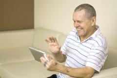Vieil homme avec les mains tatouées utilisant le bonjour de ondulation de tablette ayant image libre de droits