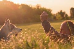 Vieil homme avec son chien dans un domaine au coucher du soleil Images stock