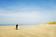 Vieil homme avec son crabot à la plage Images stock