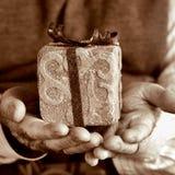 Vieil homme avec un cadeau, dans la tonalité de sépia Photos stock