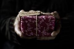 Vieil homme avec un cadeau de Noël Images stock