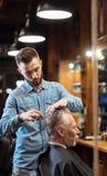 Vieil homme ayant la coupe de cheveux par le jeune spécialiste Image stock