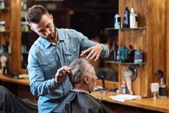 Vieil homme ayant la coupe de cheveux par le jeune spécialiste Photographie stock