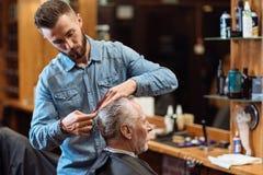 Vieil homme ayant la coupe de cheveux par le jeune spécialiste Image libre de droits