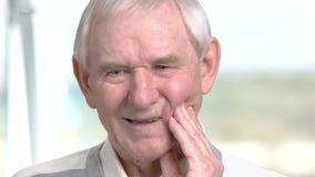 Vieil homme ayant le toohache, fond brouillé clips vidéos
