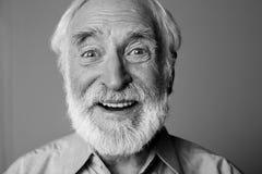 Vieil homme barbu enthousiaste regardant l'appareil-photo photographie stock libre de droits