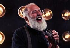 Vieil homme barbu satisfaisant avec le microphone dans des mains chantant en Th Image stock