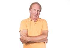 Vieil homme beau avec les mains oranges de polo croisées Photographie stock libre de droits
