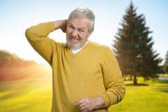 Vieil homme beau touchant de retour du cou en douleur Image libre de droits