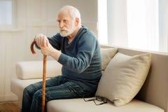 Vieil homme bouleversé se penchant sur la canne Photos stock