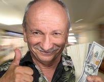 Vieil homme chanceux tenant des billets d'un dollar Photographie stock