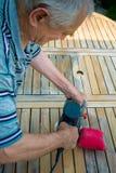Vieil homme - charpentier travaillant avec la ponceuse électrique dans le jardin Images stock