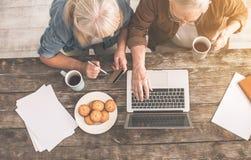 Vieil homme concentré et femme faisant des achats en ligne Photographie stock libre de droits