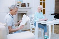 Vieil homme concentré lisant un journal merveilleux Photos stock