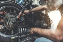 Vieil homme concentré vérifiant la motocyclette Photographie stock libre de droits