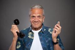 Vieil homme confus avec des téléphones Image libre de droits