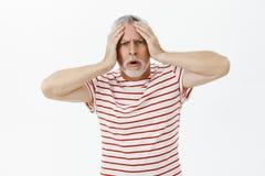 Vieil homme contrarié tracassé et choqué intense touchant la tête et la bouche ouverte de froncement de sourcils regardant cocner image libre de droits