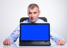 Vieil homme d'affaires au bureau avec l'ordinateur portable vide d'écran Photos libres de droits