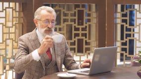 Vieil homme d'affaires avec l'ordinateur portable à la pause-café dans son concept de bureau banque de vidéos