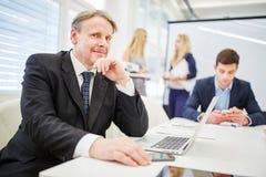 Vieil homme d'affaires avec l'ordinateur portable Images libres de droits